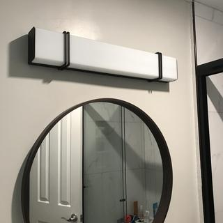 Beautiful lamp above mirror and floating sink.