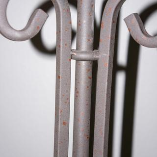 Iron scroll tray floor lamp with wood stain spatter, side view.