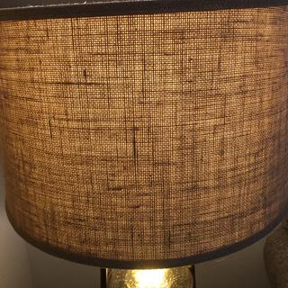 Burlap lampshade with light on.
