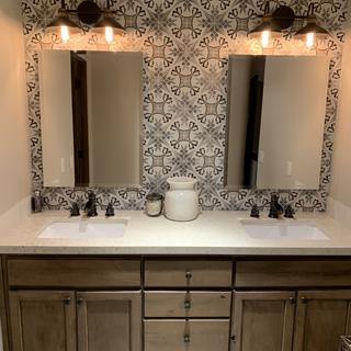 Bathroom tile, counter, faucets and lights.