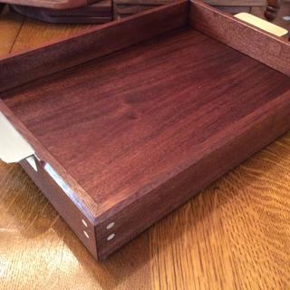 Mahogany serving tray with brass handles and matching brass rods .