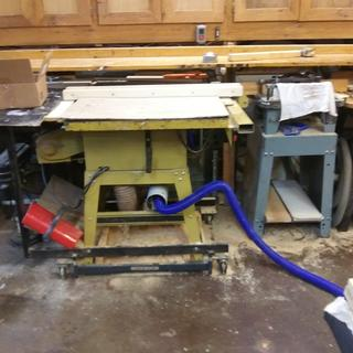 The saw comes in and out as need and so does the vac hose through a chase in the table saw stand.