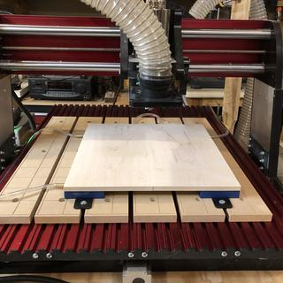 """A picture with the vacuum pads hold down a 1/2"""" thick maple piece."""