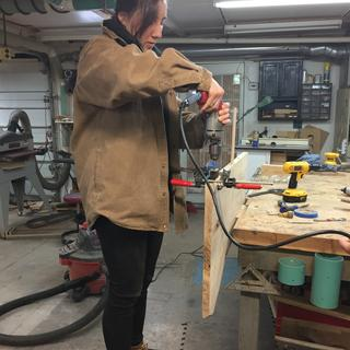 A granddaughter working on her live edge desk .