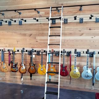 """Mounted the rail on standoffs of 1"""" black iron pipe and floor flanges to roll over the guitars."""