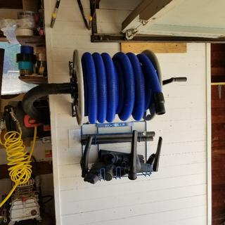 40' hose and reel hooked to an extra large vacuum cleaner in the closet behind. Accessories below.