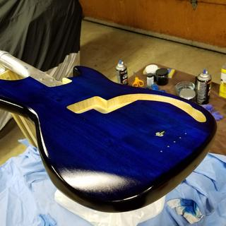 Used black and blue stains to get a burst effect on a guitar body. Finished with lacquer coats.