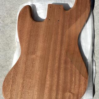 The raw wood bass guitar body of solid Mahogany.