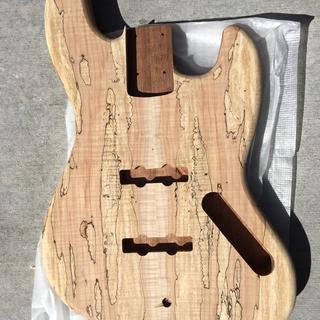 The raw wood bass guitar body with a Spalted & Flamed top.