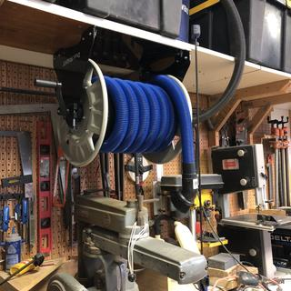 Overhead convenience. I can reach up anytime and reel out my vacuum hose and connect to bench tools.