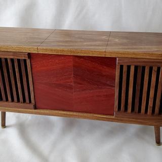 Stereo Console. Speakers behind walnut grills, center Padauk veneer, case Poplar stained walnut.