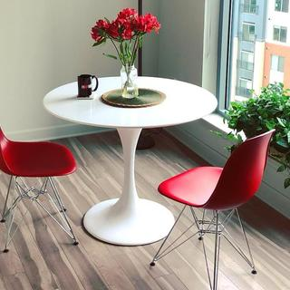 """Lippa 40"""" round white fiberglass dining table, with red Paris side chairs."""