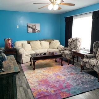 Living room with sunburst rug.