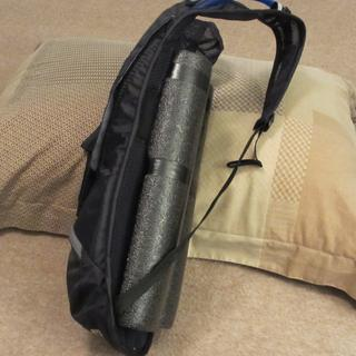 Black foam pool noodles cut and attached to provide a barrier between sweaty jersey and  pack.