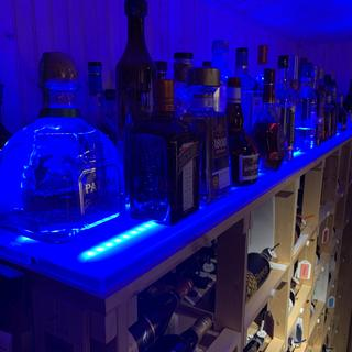 Using this shelf for an overflow liquor cabinet helps relieve pressure on the upstairs bar.