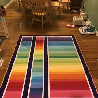 Rainbow quilt with purple border.