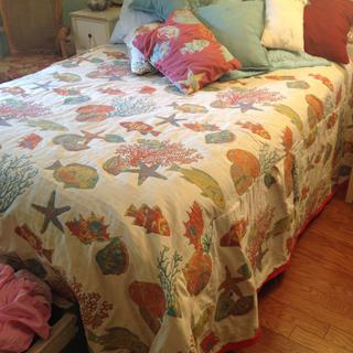 Bedspread and throw pillows with red rope trim