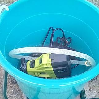 Transfer pump in bucket on cart.