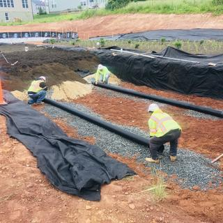 "Contractor placing 6"" N-12 under drain pipe atop approximately 1"" of #57 stone. Non woven geo textil"